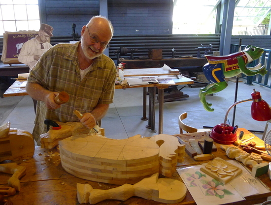 In the carving room, local artisans like Bill Miller demonstrate techniques on lightweight basswood.